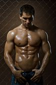 stock photo of felons  - the very muscular handsome sexy guy on netting steel fence - JPG