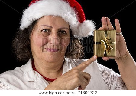 Mature Woman With Red Cap Pointing At Golden Gift