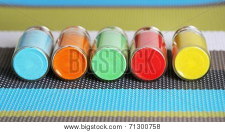 Bottles with colorful dry pigments on bright background