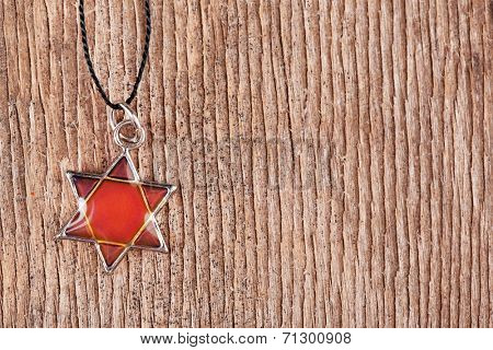 Star David pendant on wooden background