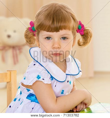 girl sitting at a table in his room.