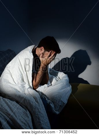 Young Man Sitting On Couch At Home Wrapped In Messy Duvet Suffering Depression