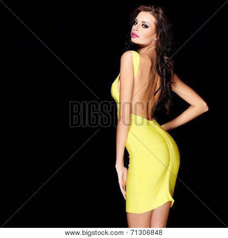 Sexy slim brunette posing in yellow dress on black background