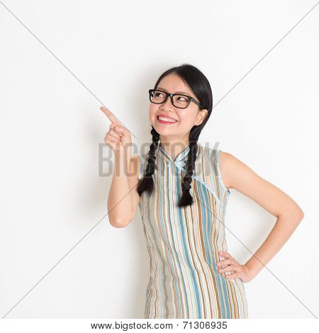 Portrait of Asian Chinese girl smiling and pointing on blank copy space, in retro revival style cheongsam, standing on plain background.