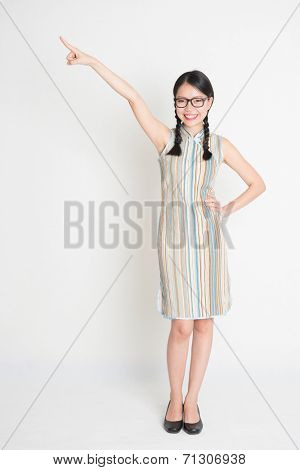Portrait of full length Asian Chinese girl smiling and pointing on blank copy space, in retro revival style cheongsam, standing on plain background.