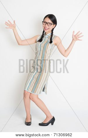 Portrait of full length surprised Asian Chinese female open arms and looking at camera, in retro revival style cheongsam, standing on plain background.