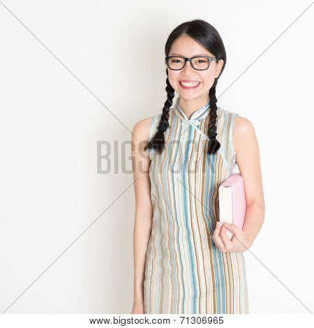 Portrait of Asian Chinese college girl hands holding text books in retro revival style cheongsam standing on plain background.