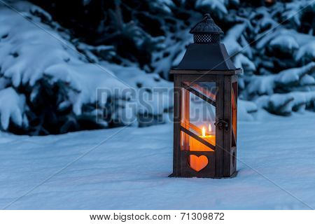 a lantern lights up in the snow at christmas. romantic light on one evening in the winter. peace and quiet