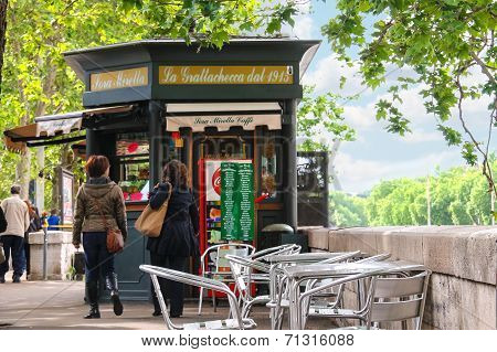 People Near The Kiosk Of A Roadside Cafe On The Waterfront Of The Tiber In Rome, Italy
