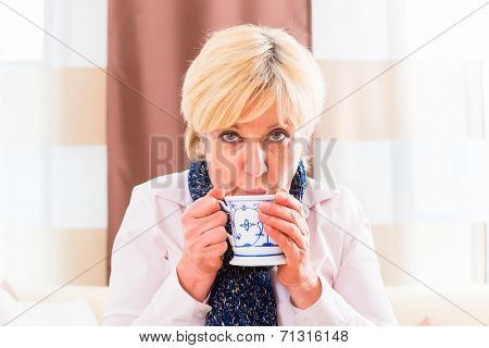 Old woman drinking tea to cure her bad cold or flu at home