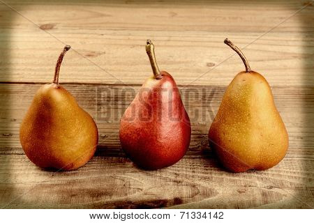 High angle closeup shot of a group of three pears on a table cloth. Bosc and Red Pears are shown, in an instagram style with vignette.