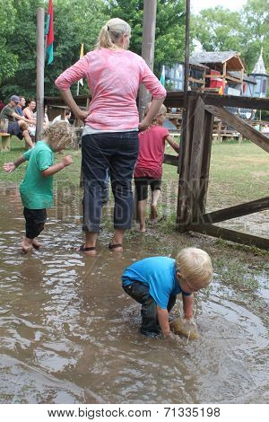 MUSKOGEE, OK - MAY 24: Kids play in water and mud after rain at the Oklahoma 19th annual Renaissance Festival on May 24, 2014 at the Castle of Muskogee in Muskogee, OK.