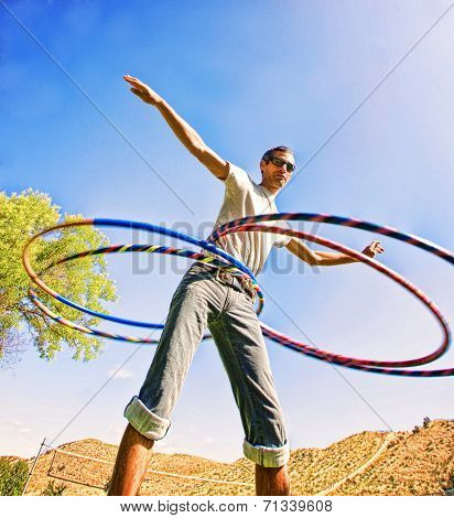 a young man hula hooping in a local park