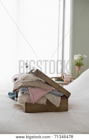 An overstuffed suitcase on bed