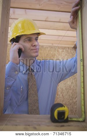 Young architect measuring a wooden beam while using cell phone at construction site