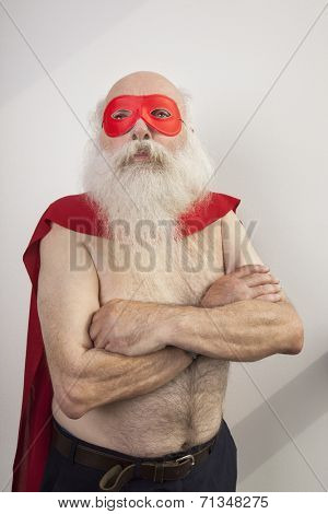 Shirtless senior man in super hero costume against white background