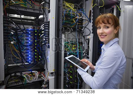 Smiling technician using tablet pc while analysing server in large data center