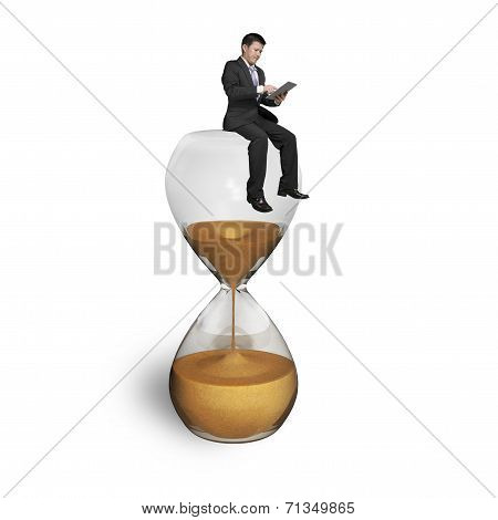 Man Using Tablet And Sitting On Hourglass