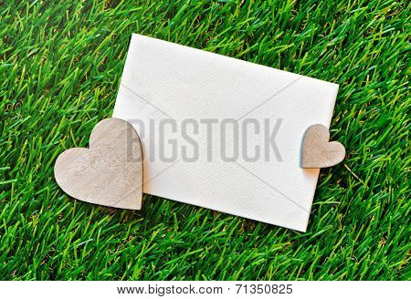 Romantic blank white valentines card lying on green grass with wooden hearts