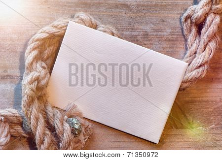 Nautical maritime background with cordage on weathered wood with blank white card and copyspace