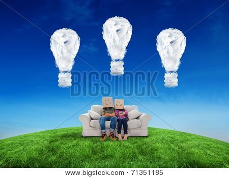 Silly employees with arms folded wearing boxes on their heads against cloud light bulbs