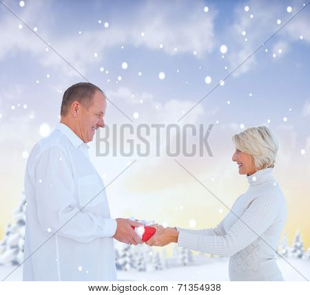 Couple exchanging gift against snowy landscape with fir trees