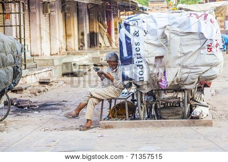 Rickshaw Man Rests And Reads News