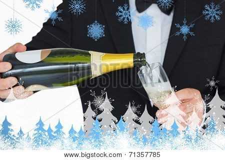 Welldressed man pouring champagne against snowflakes and fir trees