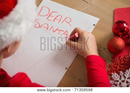Little girl writing letter to santa at christmas at home in the living room