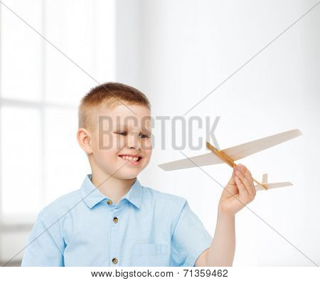 dreams, future, hobby, home and childhood concept - smiling little boy holding wooden airplane model in his hand over white room background