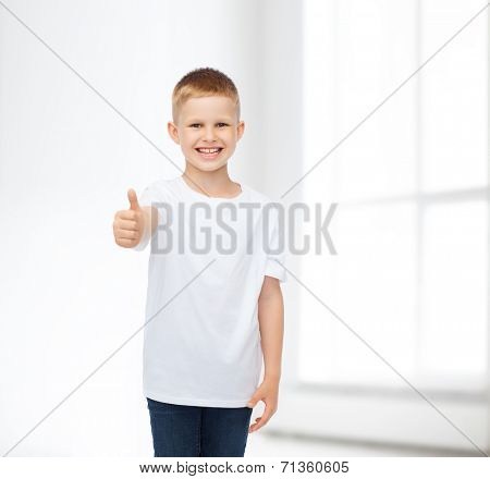 advertising, people, gesture and childhood concept - smiling little boy in white blank t-shirt showing thumbs up over white room background