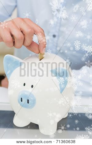Closeup mid section of a man putting coin into piggy bank against snow falling