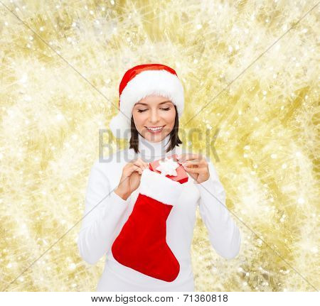 christmas, winter, happiness, holidays and people concept - smiling woman in santa helper hat with small gift box and stocking over yellow lights background
