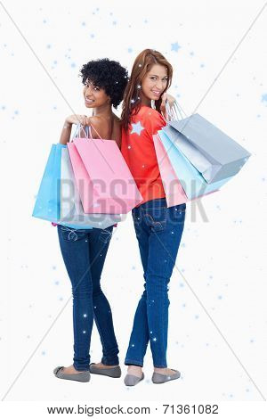 Smiling teenagers looking behind them after shopping against snow falling