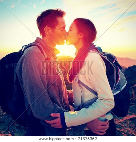 Kiss - couple kissing romantic at hiking sunset sharing embrace enjoying sunshine and love on beautiful hike in mountain nature landscape. Young interracial couple, Asian woman, Caucasian man in love.