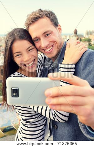 Selfie smartphone self-portrait by happy couple. Lifestyle photo with young friends or lovers taking picture with smart phone. Multiracial Asian woman and Caucasian man.