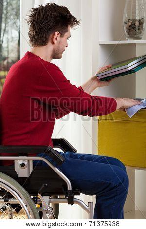 Man On Wheelchair Dusting Shelves