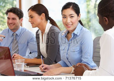 Group Of Businesspeople Meeting Around Boardroom Table