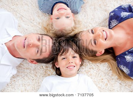 Cheerful Family Lying In Circle On The Wall-to-wall Carpet