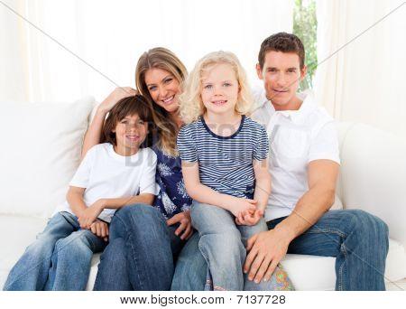 Família alegre, assistindo televisão, sentado no sofá