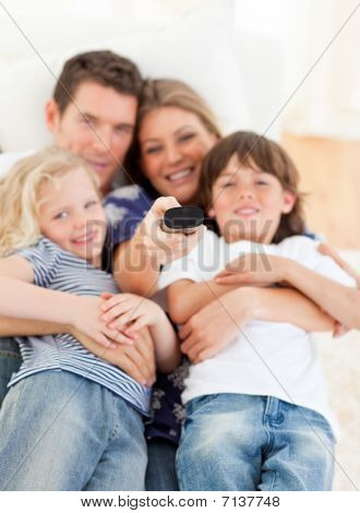 United Family Watching Television Sitting On Sofa