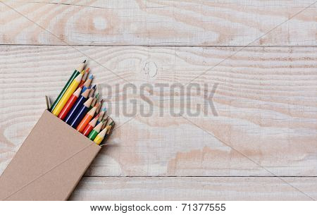 High angle shot of a box of multi-colored pencils on a white wood table. The pencils are partially out of the box and at an angle in the bottom left corner, with copy space.