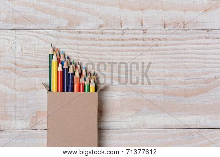 High angle shot of a box of multi-colored pencils on a white wood table. The pencils are partially out of the box set to one side leaving copy space.