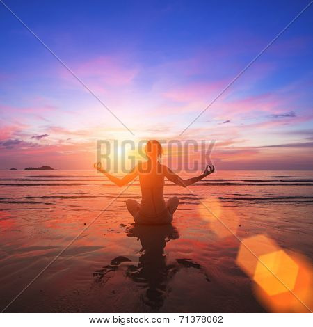 Girl practicing yoga on the ocean side, the silhouette in the rays of awesome sunset.