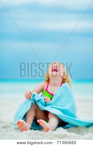 Portrait Of Laughing Baby Girl In Towel Sitting On Beach