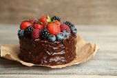 picture of cream cake  - Tasty chocolate cake with different berries on wooden table - JPG
