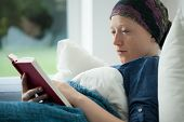 pic of lonely woman  - Woman with cancer reading a book in bed - JPG
