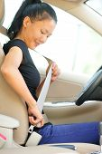 stock photo of seatbelt  - woman driver buckle up the seat belt before driving car - JPG