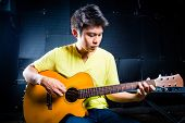 stock photo of guitarists  - Asian professional guitarist playing acoustic guitar music in recording studio - JPG