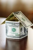 stock photo of x-rated  - a house made from bills of 100 dollars dof f/x selective focus ** Note: Shallow depth of field - JPG